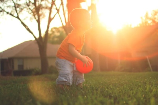 toddler-plays-with-ball-in-sun-outdoor-games-petit-early-learning-journey