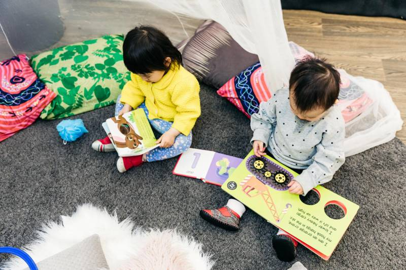 Two children at Petit Forest Hill read together beneath a cosy tent. Photos of activities are effective at sharing information with parents in child care.
