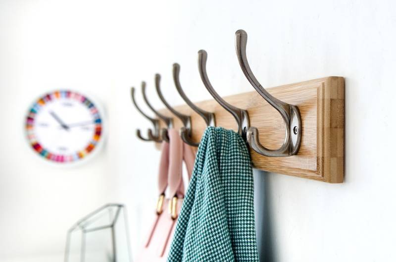 A wooden DIY home project coat rack with six hooks hangs on the wall. It holds a couple of pieces of clothing and has a colourful clock on the background.