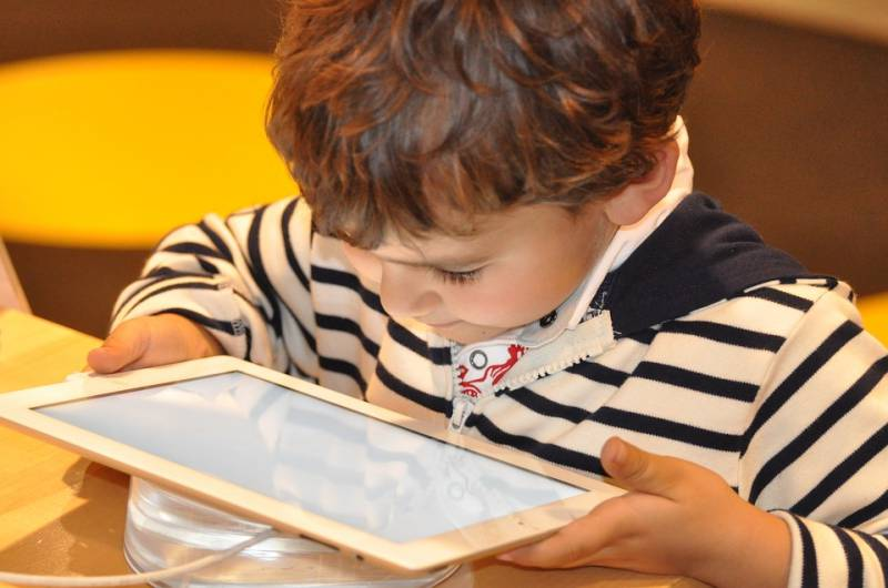 A toddler in a striped shirt searches his tablet for his favourite YouTube channels for kids.