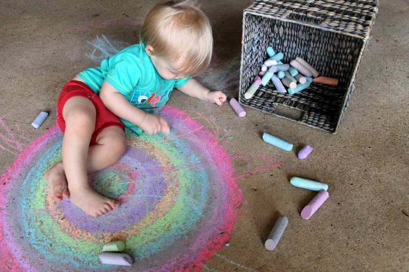 A toddler colours in an art project on cement floor with chalk.