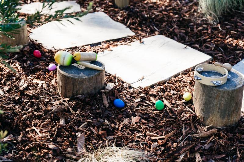 Group of musical instruments on tree stumps wait for children to create a DIY project.
