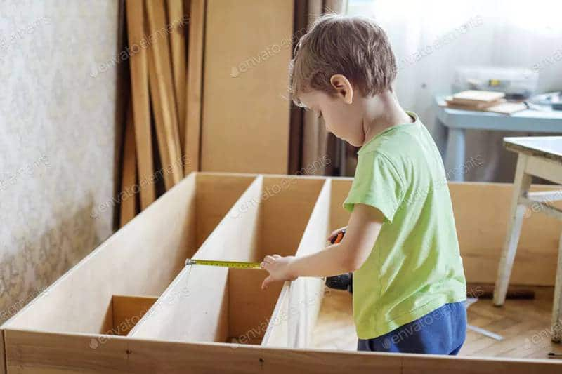 Preschooler uses a tape measure on shelves to help Dad with his DIY Projects.