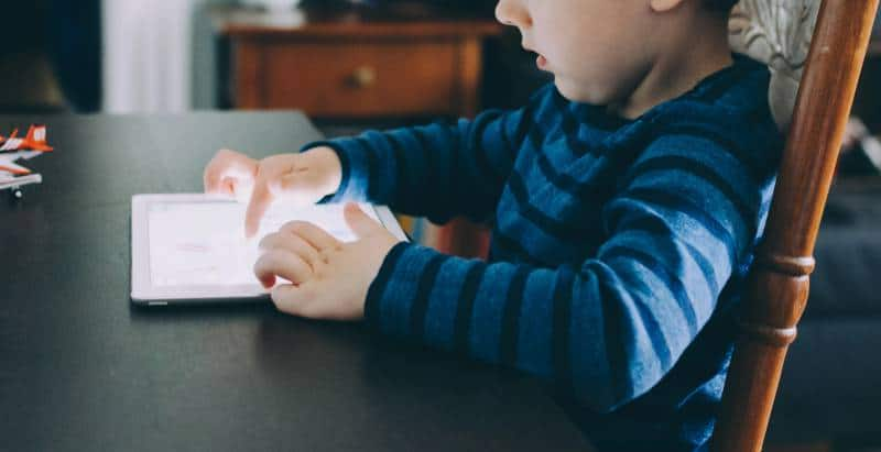Child sits at table playing on an IPad instead of going to bed and sleep training for toddlers.