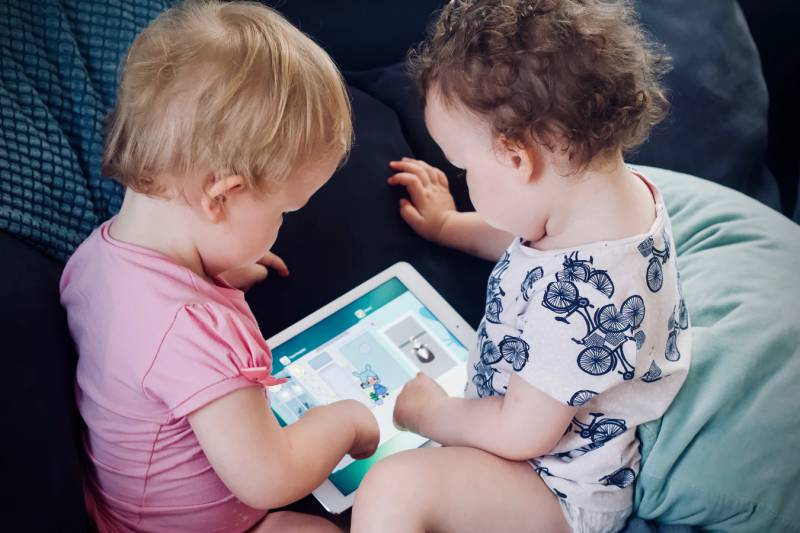 Two toddlers play with a tablet while listening to YouTube nursery rhymes.