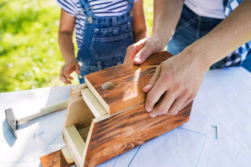 Child helps Dad build a do-it-yourself birdhouse on an outdoor table.