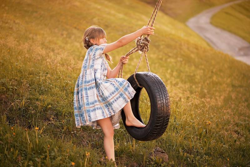 A young female child stands on a grassy hill and readies herself to enjoy a Dad DIY project of a tyre swing.