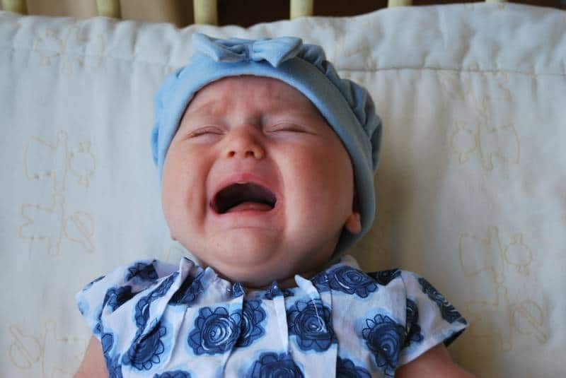 Child dressed in blue cries for attention. A sleep training technique is to let the baby cry for longer periods of time.