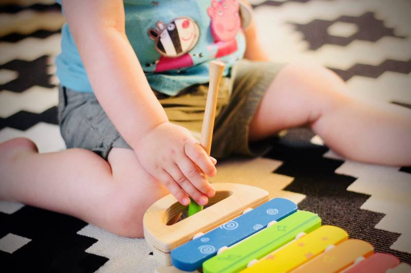 A toddler with Peppa Pig t-shirt sits on the floor. He plays with a toy musical instrument and inspired by YouTube kids stories.