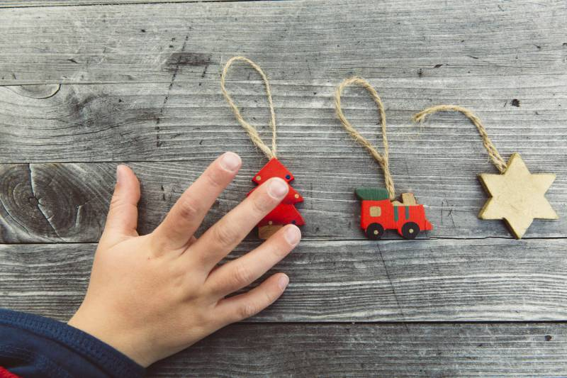 Child's hand reaches out to play with three DIY Xmas decoration, a tree, truck and star.