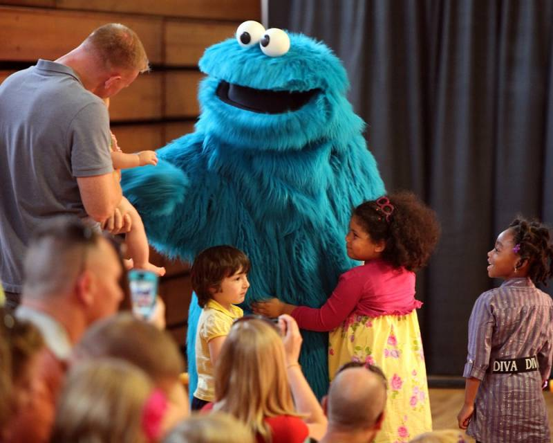 A child hugs the Cookie Monster character on stage while other children wait their turn. Cookie Monster is one of many popular characters on Sesame Street Youtube.