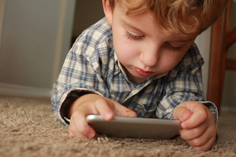 A young male child uses a digital phone to access educational videos for kid.