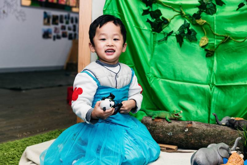 A child dresses up in a blue dress with zoo animal toys for a homemade project.
