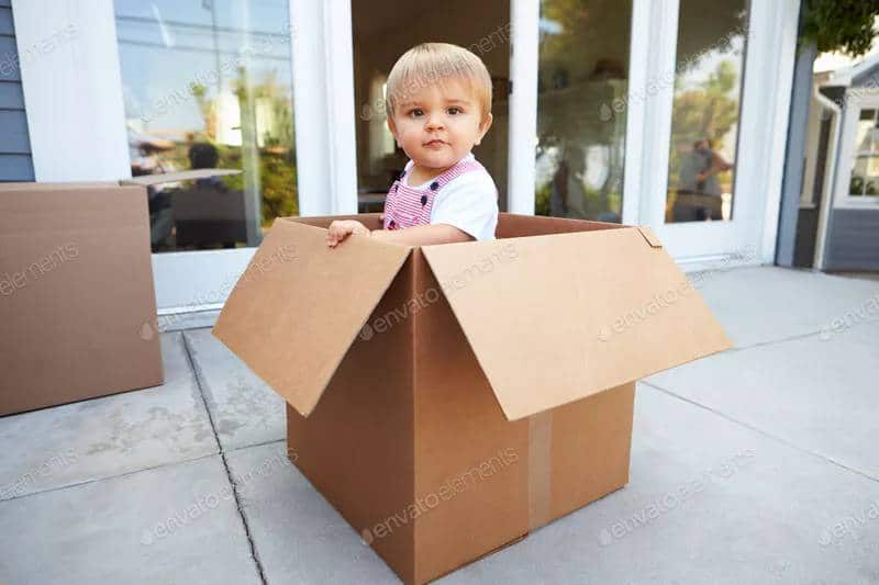 A young child stands inside a moving box outside his home. Cardboard boxes make cheap building projects for kids.