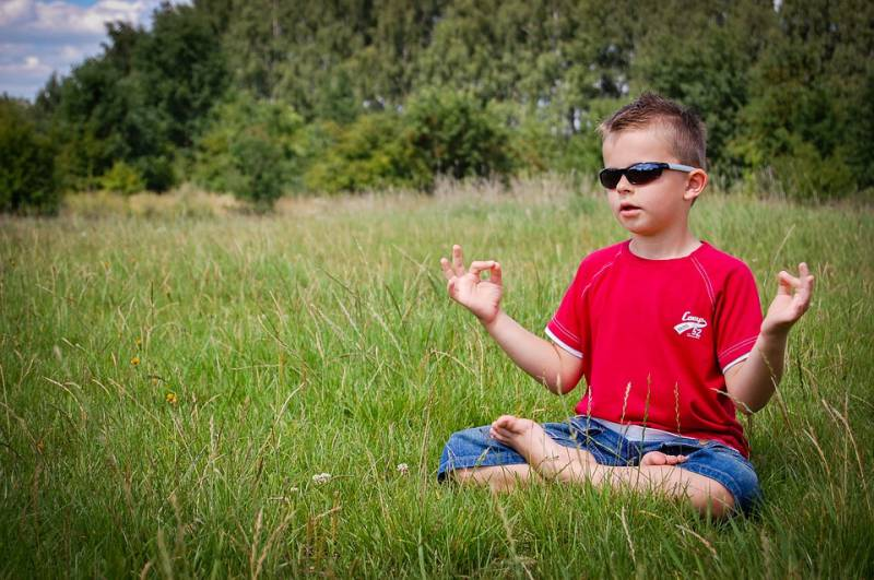 Boy in red shirt with folded legs and zen fingers, meditates on what is mindfulness.