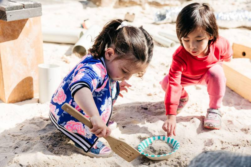 Two children scoop sand into a bowl with a wooden egg-flip as they participate in spontaneous play-based learning.