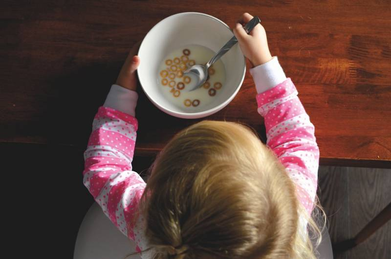 A fussy eater looks into a bowl of cereal.