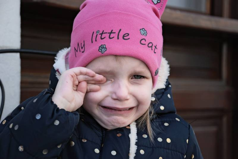 An ideal nap time is when a young child shows signs of tiredness like this little toddler in a pink hat who rubs her eyes and cries.