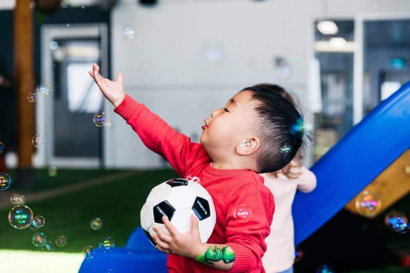 Young toddler holding a ball and reaching out to catch a bubble expresses his enjoyment with gestures - expressing one of the five learning outcomes.