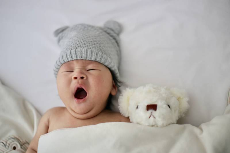 Baby yawns besides his teddy, both ready for nap time.