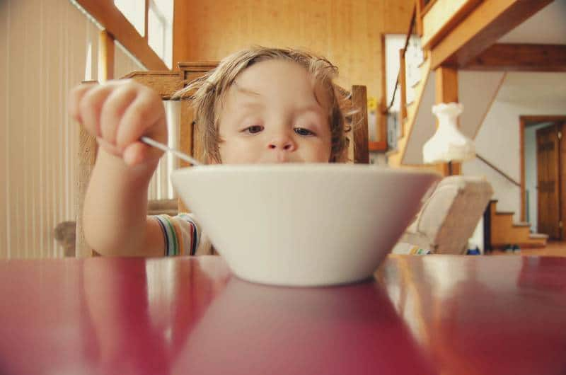 Child stares into bowl with a healthy snack for picky eaters.