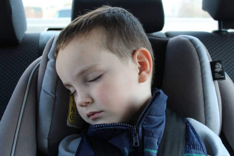 Young boy falls asleep in his car seat on a short ride, a sign your toddler needs a nap.