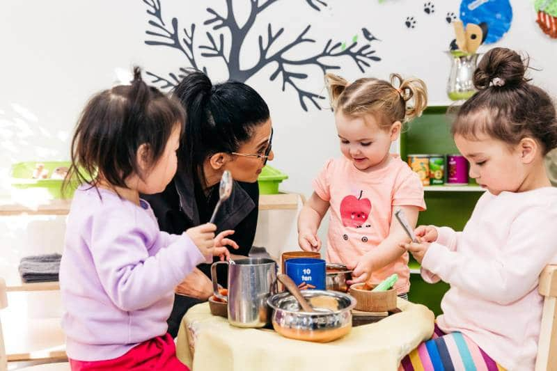 Three toddlers take the lead to play around the kitchen table as part of an early learning program.
