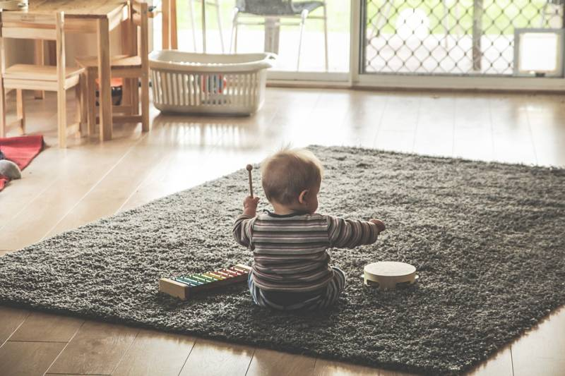 Infant sits between xylophone and tambourine in music instrument game