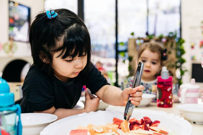Toddler selects fruit from a plate at Petit Forest Hill, a healthy meal for fussy eaters.