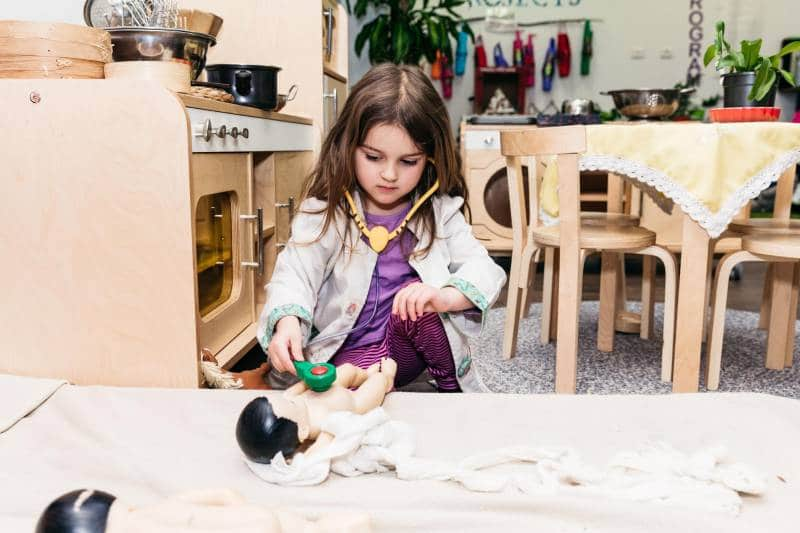Child plays at being a doctor developing her creativity as a benefit of play-based learning.