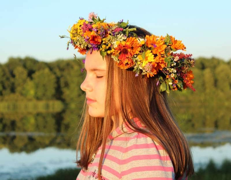 Teen with flower wreath relaxes and soaks up the Sun. Quiet meditation increases mindfulness for kids.