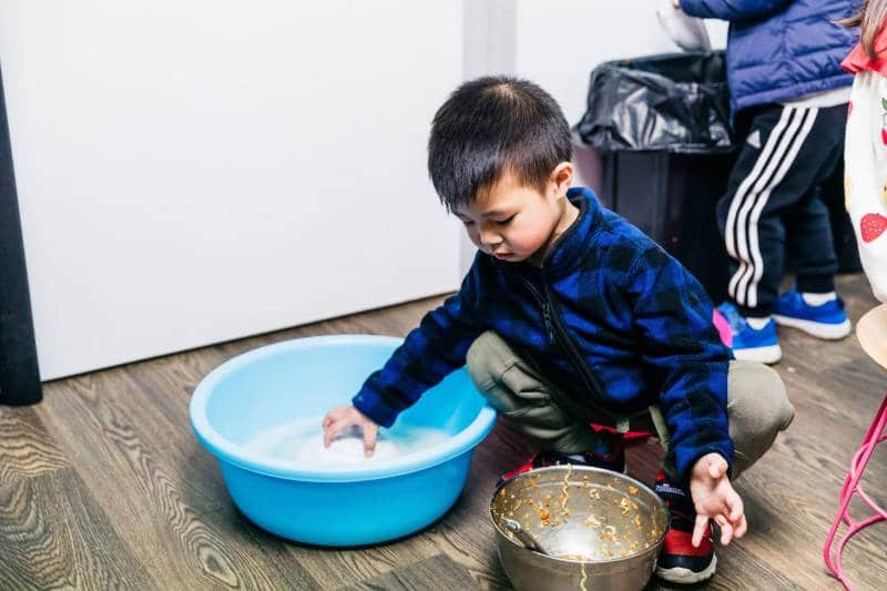 Toddler crouches on floor washing a plate in tub of soapy water, Petit ELJ creates activities that embrace the learning strategies and practices of the EYLF.