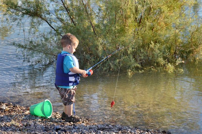 Child uses a rod with red lure on the bank of a river to catch food for fussy eaters.