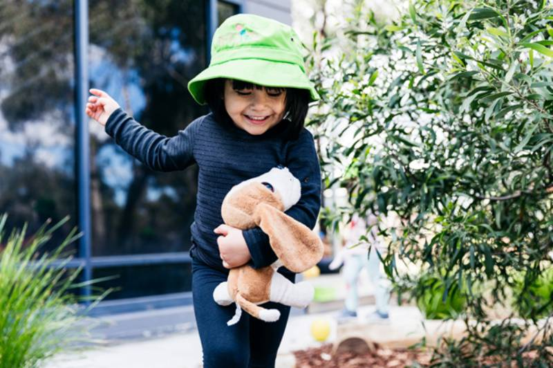 Child plays outdoors holding a special cuddly toy