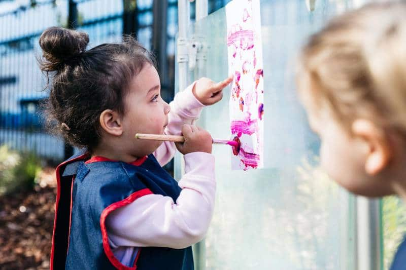 Children paint outdoors to show why art is important for their growth.