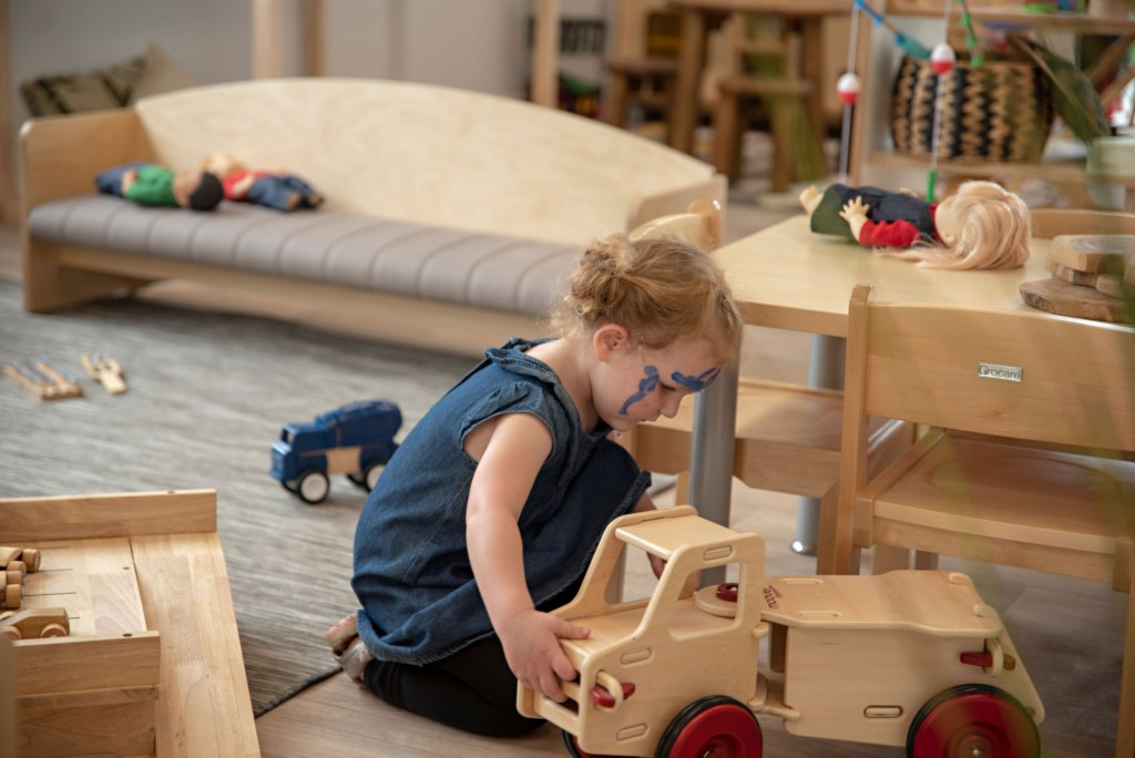 kid playing wooden toy car