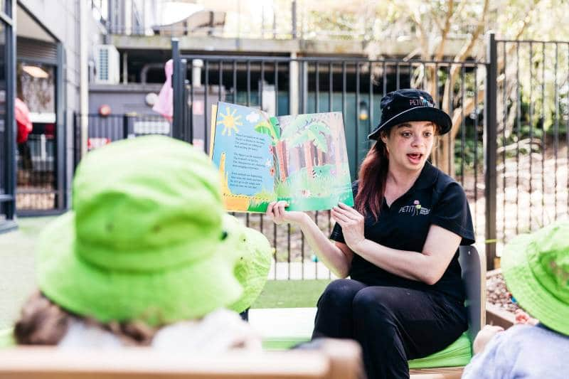 A Petit Early Learning Journey Educator reads stories to kids in an outdoor setting displaying illustrations