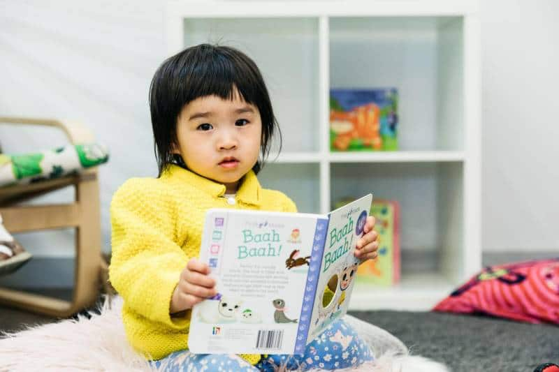 Young girl in yellow shirt reads an Australian picture books at a Petit ELJ centre