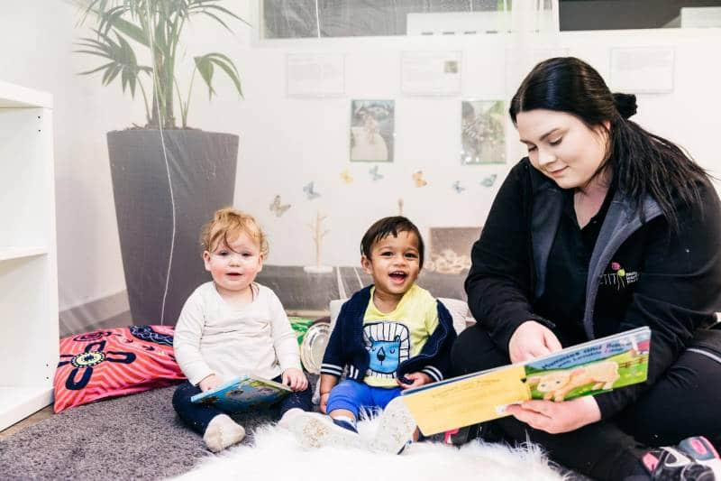 Two children enjoy the reading of a toddler book by an Educator at a Petit ELJ centre