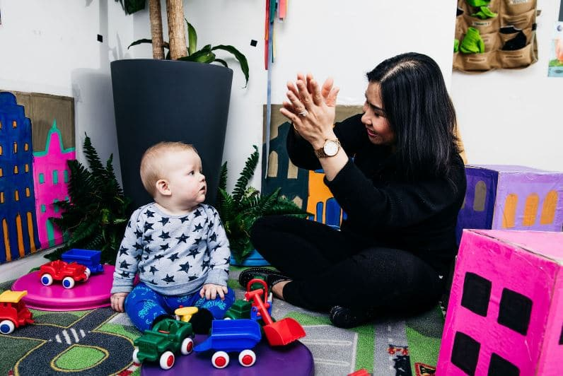Early Childhood Educator inspires a baby with play-based learning.