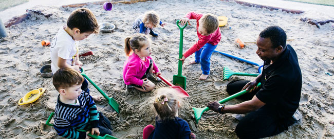 educatior in sandpit with children