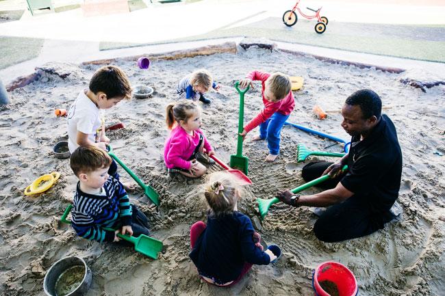 educatior in sandpit with children