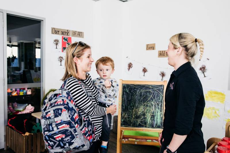 Mum in front of a popular chalkboard talking to an Educator about a tour of a childcare centre near her