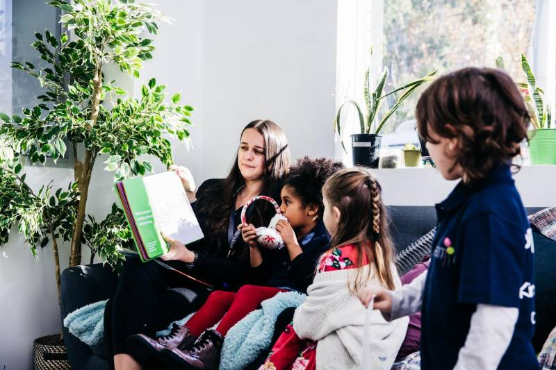 Educator and children read a picture book together. Distracting your child with a book can provide pain relief for children.