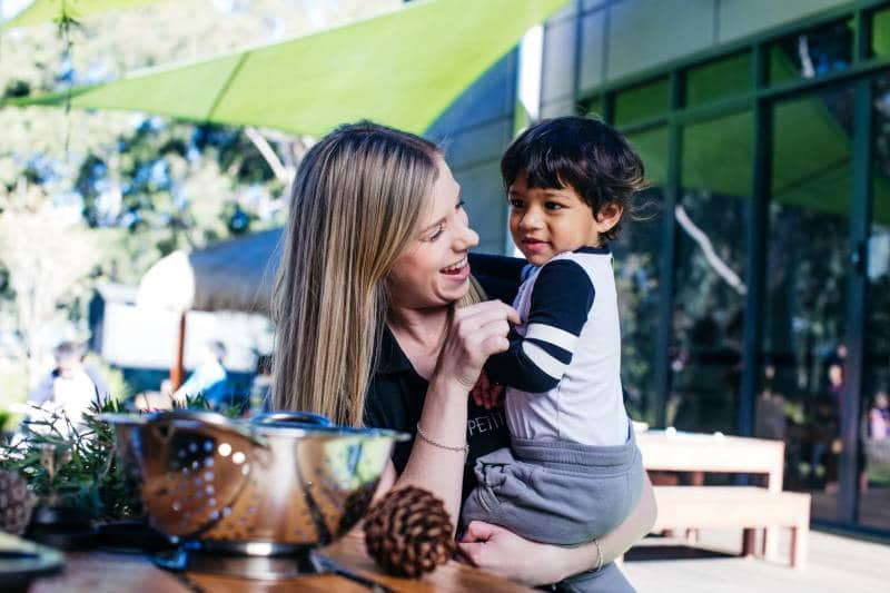 Educator cuddles a toddler in an outdoor environment where cuddles are always preferred for trips and falls than children's ibuprofen.