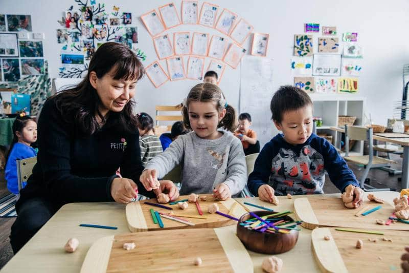 Educator works with two children on art projects that can take a child's mind off momentary pain instead of giving pain medication.