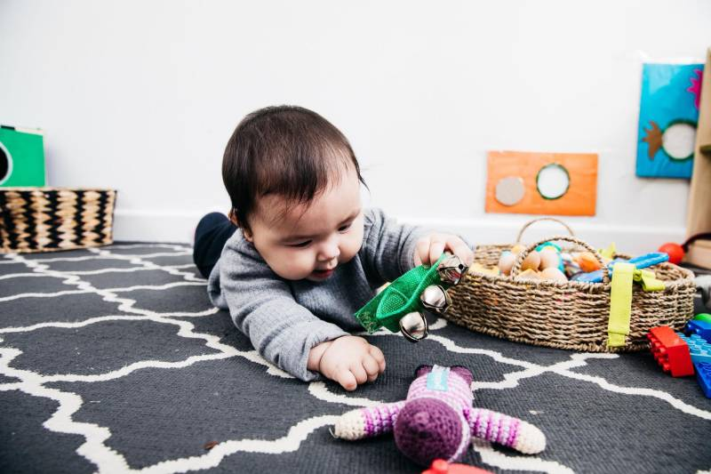Baby plays on a mat ready to do more with newborn baby stuff.