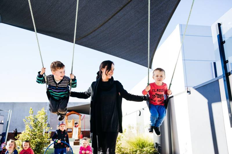 Educator pushes two children on a swing. Demonstrating passion is a key attribute in child care interviews.