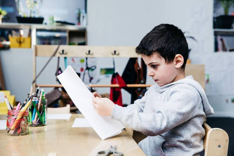 Young boy sits at a desk looking at paper activity introducing science for preschoolers.