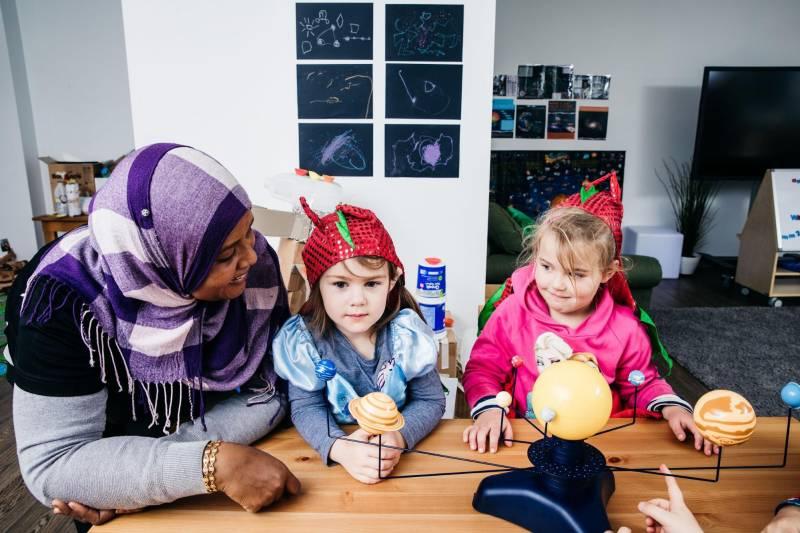 Educator and children observe solar system model and light in STEM for preschoolers.